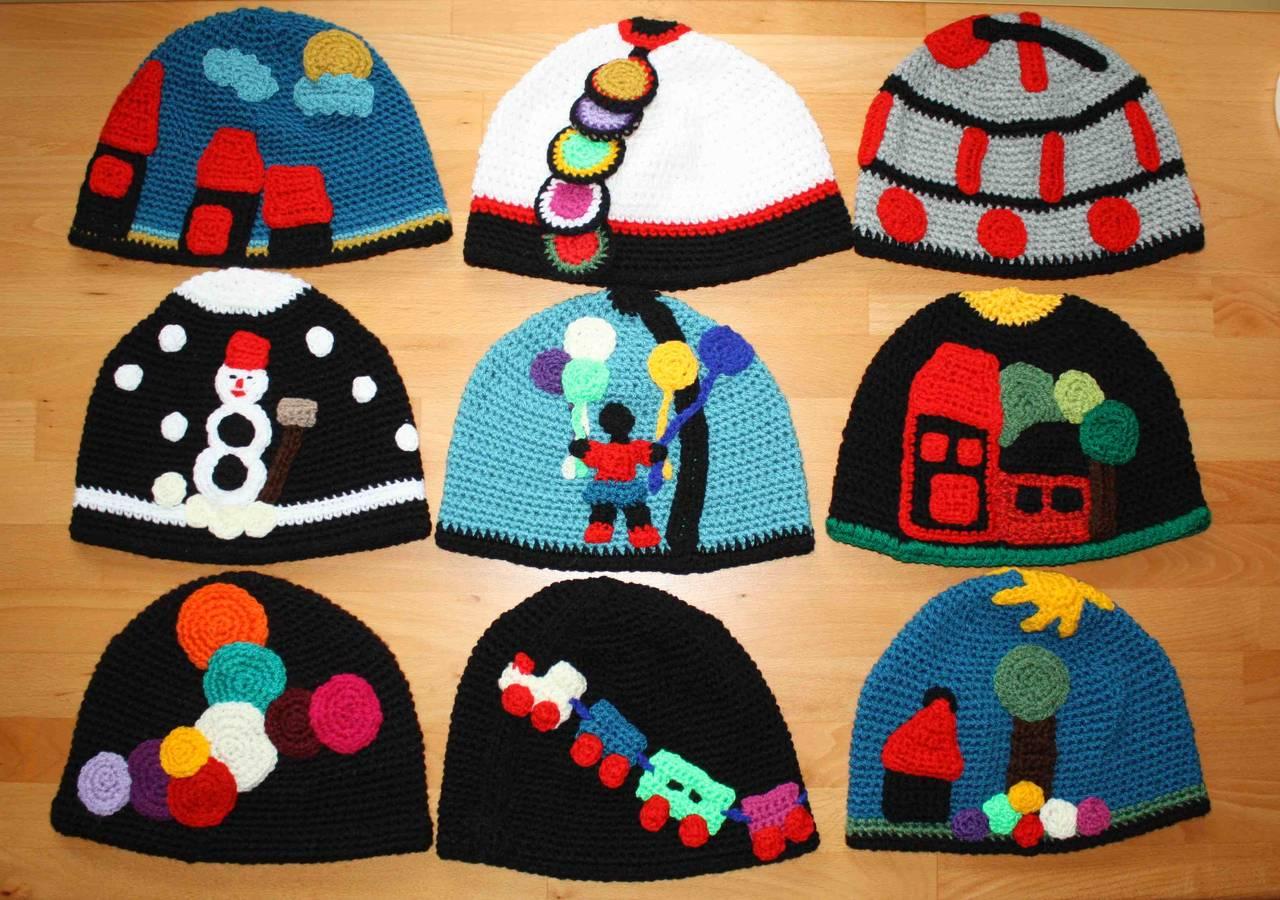 Gehäkelte Häuser, Sonne, Wolke, Zug, Schnemann und Schneeflocken, Luftballons und Bäume als Applikationen auf der Mütze