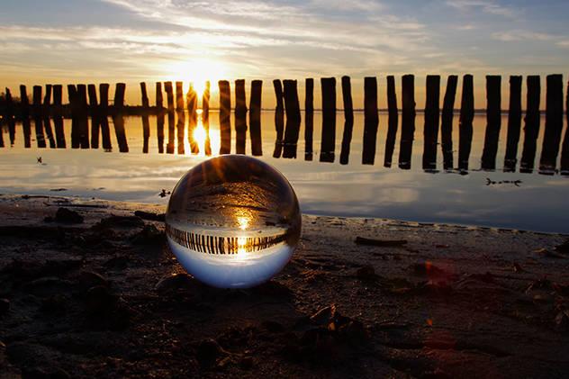 Ein schönes Naherholungsgebiet in Niedersachsen, der Dümmer See, hier ein Sonnenuntergang, mit Holzbohlen im Gegenlicht, welches sich in einer Kugel wiederspiegelt.