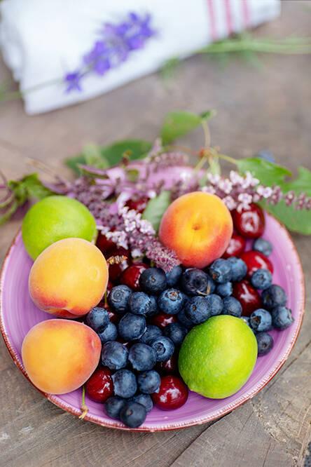 Bunter sommerlicher Obstteller mit Heidelbeeren, Pfirsich, Aprikosen, Limetten und Kirschen