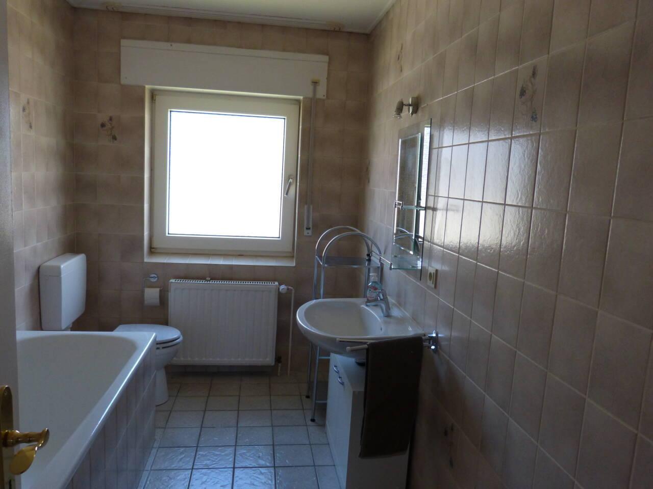 Das Badezimmer ist mit Toilette, Waschtisch, Badewanne und Dusche ausgestattet.