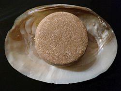Hellbraune Haarseife in Zylinderform auf einer Muschel mit eingewachsenen Perlen