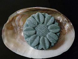 Lila Haarseife in Blütenform auf einer Muschel mit eingewachsenen Perlen