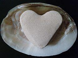 Weiße Haarseife in Herzform auf einer Muschel mit eingewachsenen Perlen
