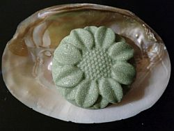Grüne Haarseife in Blütenform auf einer Muschel mit eingewachsenen Perlen